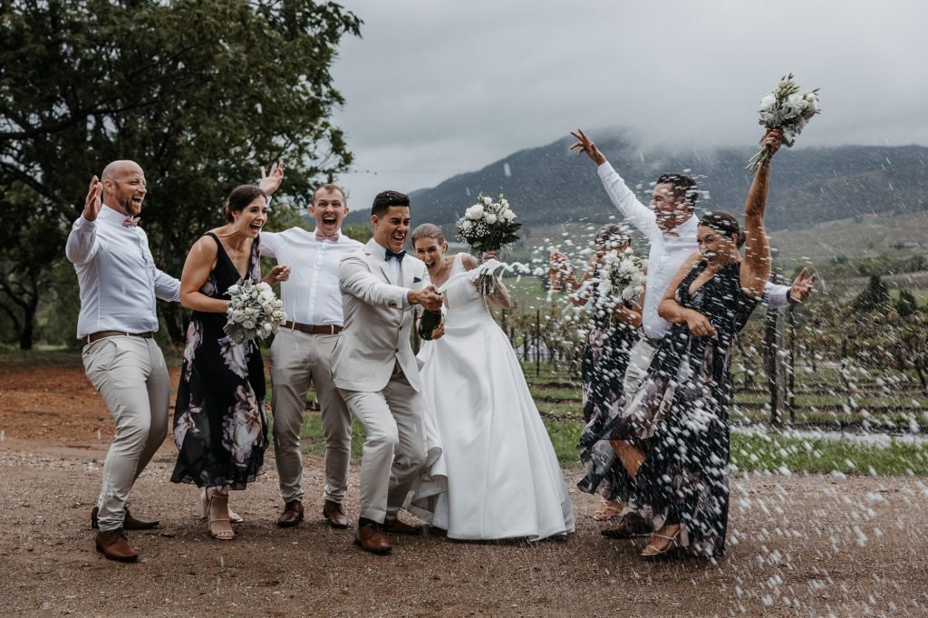 bridal party popping the bottle of bubbles